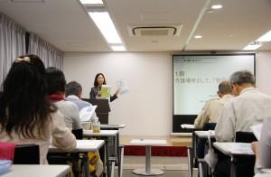 1部で話をするパオッコ太田理事長 新しい冊子を説明中